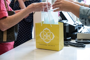 """Two people exchanging a yellow paper bag of """"Kenden Scott"""" on a store counter"""