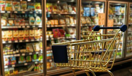 Gold shopping cart infront of a frozen food fridge
