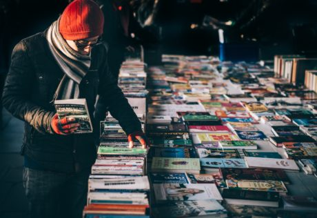 Warmly dressed person going through a table of books with a gloved hand