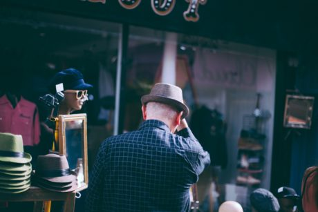 Back view of a man in a brown hat and plaid blue shirt