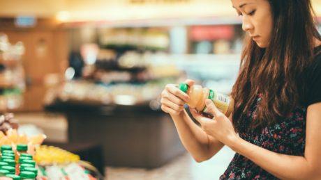 Women reading label of orange juice bottle