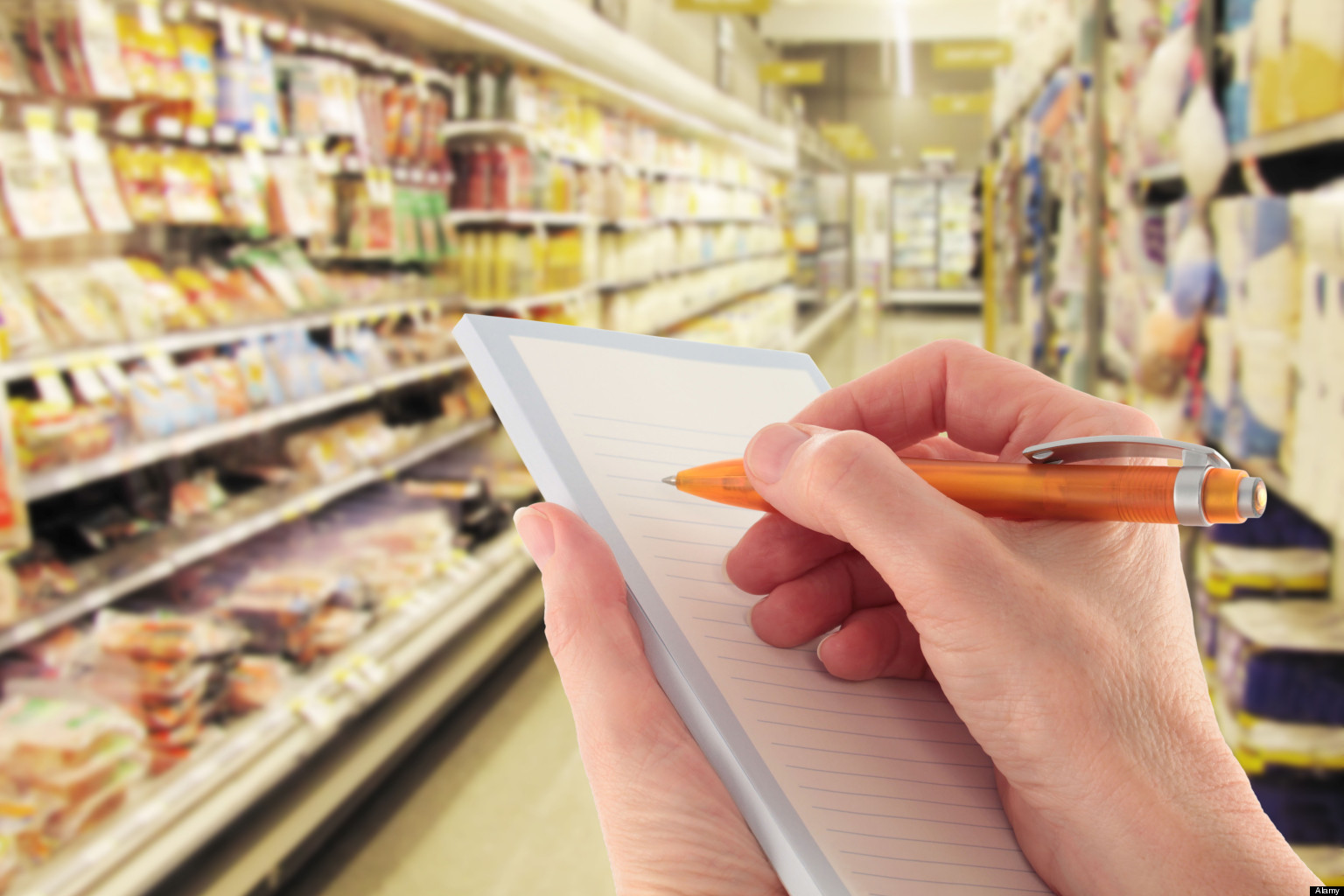 Person holding pen to write shopping list on notepad