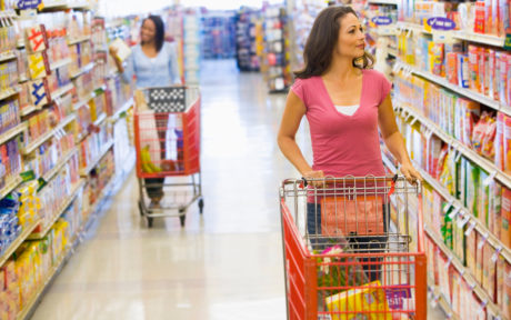 Women pushing shopping carts in the supermarket aisle